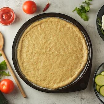 Rauw deeg en verse ingrediënten voor veganistische pizza. kopieer ruimte.