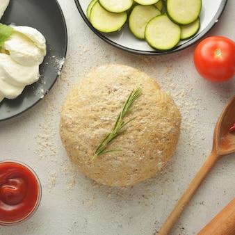 Rauw deeg en verse ingrediënten voor veganistische pizza.