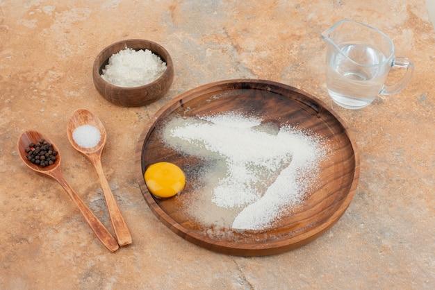 Rauw ei met lepels en houten bord.