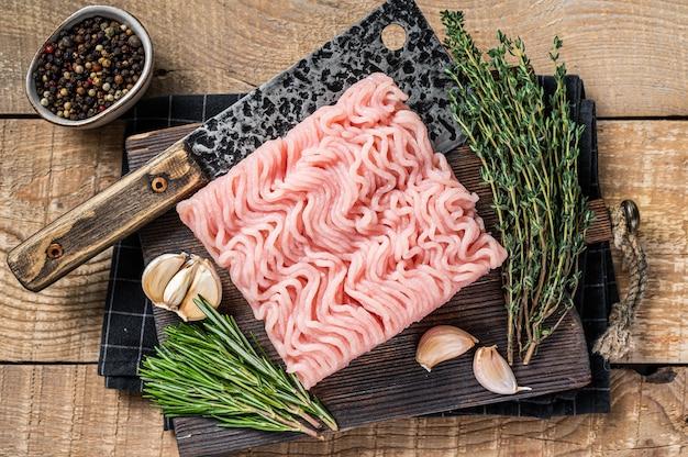Rauw gehakt kip en kalkoenvlees op houten snijplank met slagersmes. houten achtergrond. bovenaanzicht.