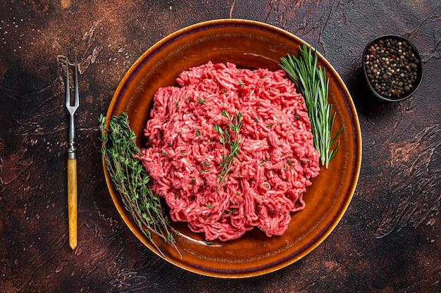 Rauw gehakt rundvlees en lamsvlees op een rustieke plaat met kruiden. donkere achtergrond. bovenaanzicht.