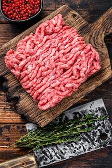 Rauw gehakt rundvlees, gemalen vlees met kruiden en specerijen op een houten snijplank. donkere houten achtergrond. bovenaanzicht.
