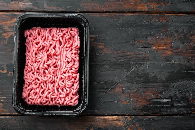 Rauw gehakt vlees in een zwarte plastic container, op oude donkere houten tafel