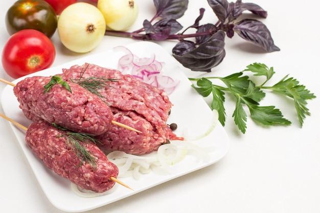 Rauw gehakt vlees op houten spiesjes en gehakte uienringen op witte plaat. tomaten, uien en basilicumtakjes op tafel. witte achtergrond. plat leggen