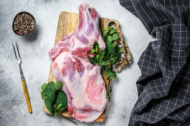 Rauw geitenschoudervlees klaar om te bakken met knoflook, munt