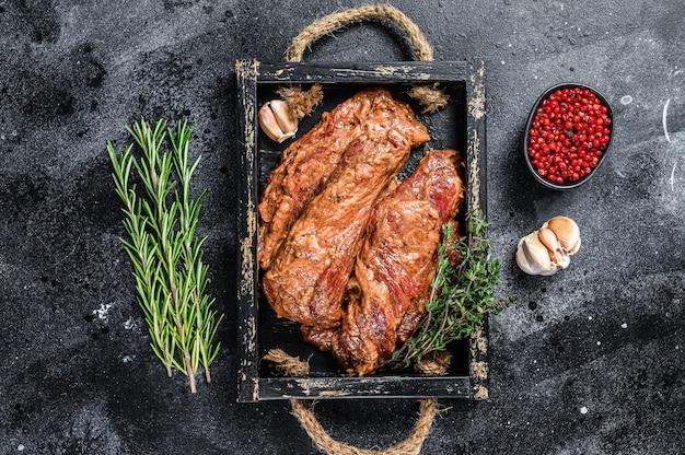 Rauw gemarineerde borstlapjes vlees in een houten dienblad met kruiden