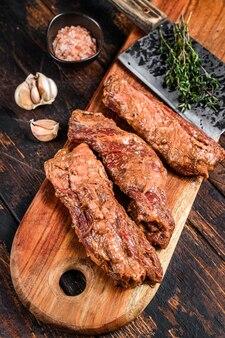 Rauw gemarineerde roklapjes vlees in bbq-saus op een houten snijplank met kruiden