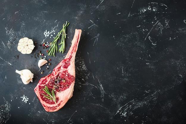 Rauw gemarmerd vlees steak, kruiden, kruiderijen, rustieke stenen achtergrond.