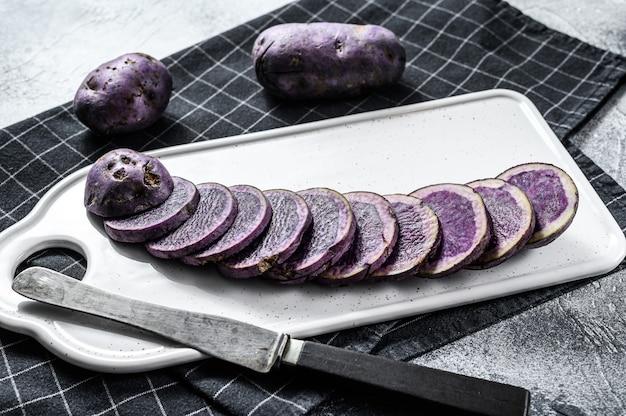 Rauw gesneden violet aardappelen op een witte snijplank. grijze achtergrond. bovenaanzicht