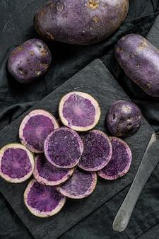 Rauw gesneden violet aardappelen. zwarte achtergrond. bovenaanzicht