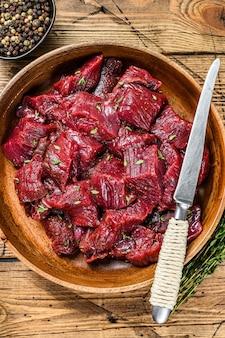 Rauw gesneden wild hertenvlees voor een goulash in een houten bord.