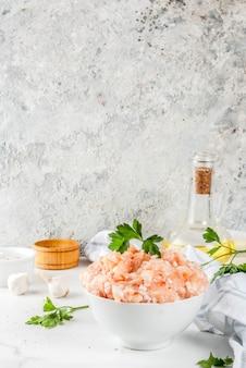 Rauw kip of kalkoengehakt in witte kom, met olie, kruiden en kruiden op lichte achtergrond. kopieer ruimte.