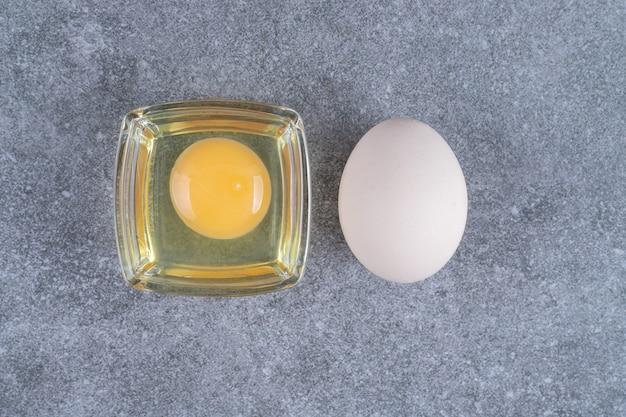 Rauw kippen wit ei met dooier op een marmeren oppervlak
