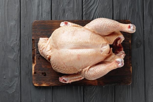 Rauw kippenkarkas op houten plaat close-up
