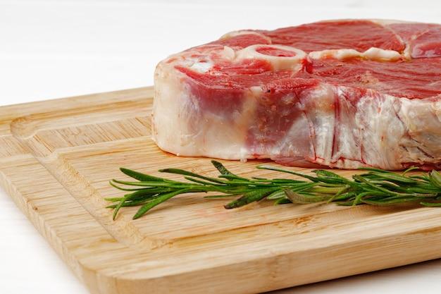 Rauw lamslapje vlees aan boord op witte houten tafel