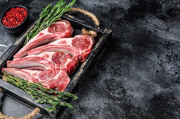 Rauw lamsvlees hakt steaks in een houten bakje