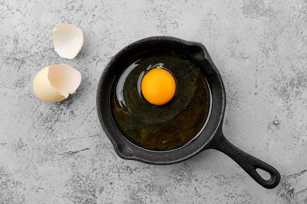 Rauw ongekookt ei in kleine gietijzeren koekenpan