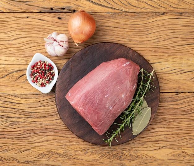 Rauw oog rond vlees over houten bord met kruiden.