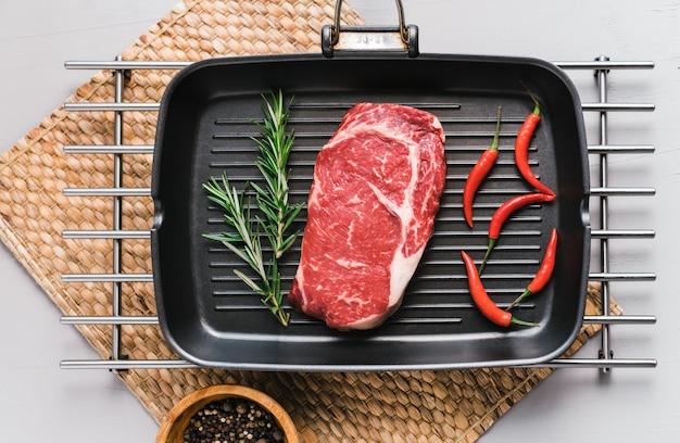 Rauw rib eye biefstuk op zwarte grillpan met chili peper en rozemarijn