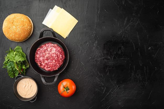 Rauw rundergehakt burger steak schnitzels met ingrediënten en broodjes, op zwarte stenen tafel, bovenaanzicht plat gelegd