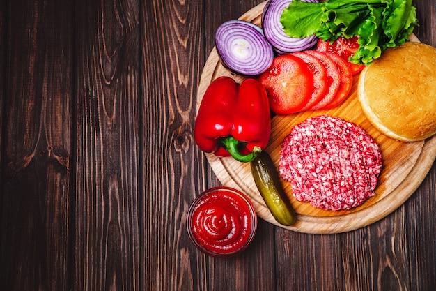 Rauw rundergehakt vlees hamburger steak koteletten met kruiden, kaas, tomaten, salade en broodje op vintage houten planken