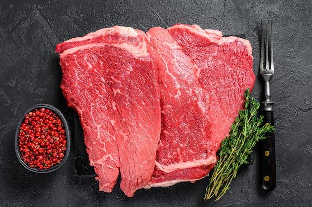 Rauw rundvlees biefstuk op een marmeren bord. zwarte achtergrond. bovenaanzicht.
