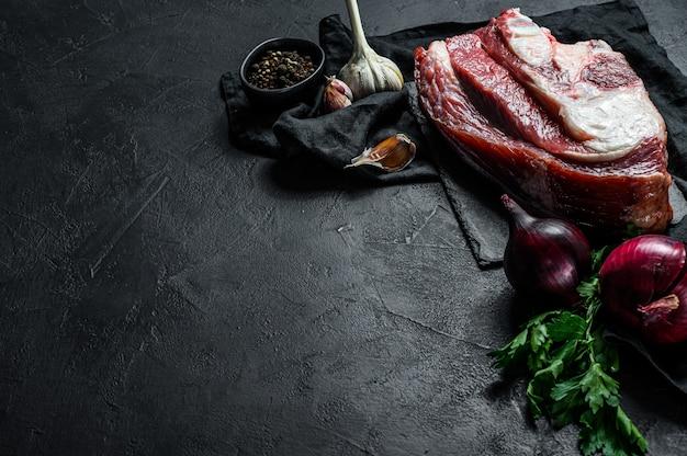 Rauw rundvlees met been op zwarte muur. bovenaanzicht. ruimte voor tekst