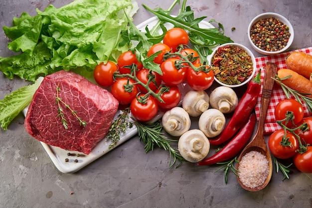 Rauw rundvlees met kruiden en rozemarijn. verse ingrediënten voor gezond koken