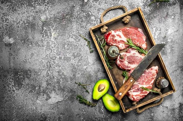 Rauw rundvlees met kruiden en specerijen. op rustieke achtergrond.