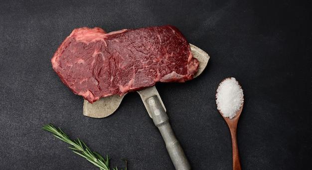 Rauw stuk biefstuk ligt op een ijzeren mes, zwart oppervlak. klassieke steak, bovenaanzicht