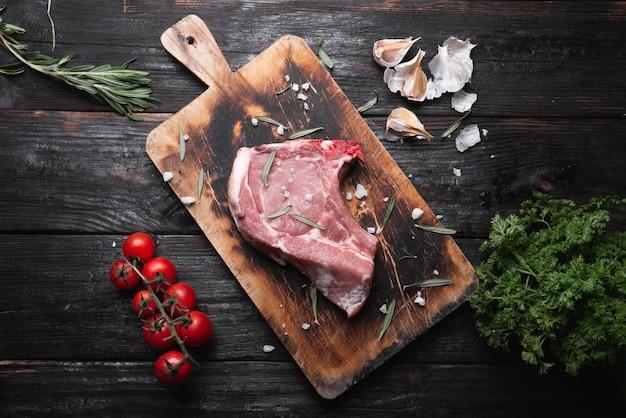 Rauw stuk vlees ligt op tafel, geurige specerijen, tomaten en kruiden.