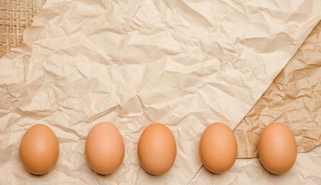 Rauw van verse bruine kippeneieren op gerimpeld kraftpapier.