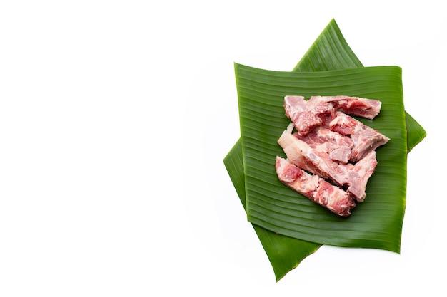 Rauw varkensvlees bot op bananenbladeren op witte achtergrond.