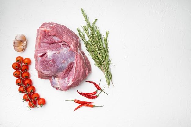 Rauw varkensvlees met kruidenset, op witte stenen tafelachtergrond, bovenaanzicht plat, met kopieerruimte voor tekst
