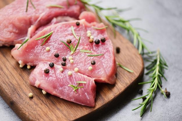 Rauw varkensvlees op houten snijplank op de keukentafel voor het koken van varkensvlees steak geroosterd of gegrild met ingrediënten kruiden en specerijen vers varkensvlees