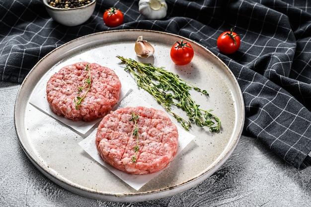 Rauw varkensvlees pasteitje, gehakt koteletten op een snijplank. biologisch gehakt. grijze achtergrond. bovenaanzicht