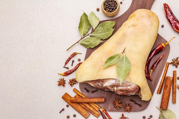 Rauw varkensvlees - spronggewricht, knokkel of been. traditioneel ingrediënt voor eisbein. vers vlees, droge kruiden en groenten