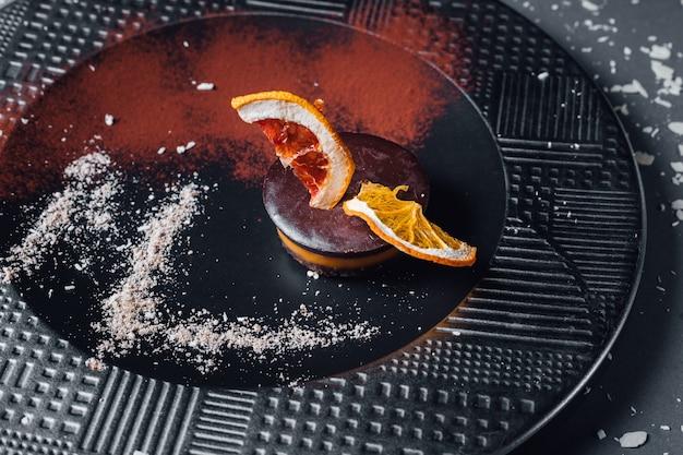 Rauw veganistisch dessert van gedroogd fruit, noten en romige cashew-samenstelling, kokosboter, johannesbrood. op de plaat, geïsoleerd op zwarte achtergrond, close-up