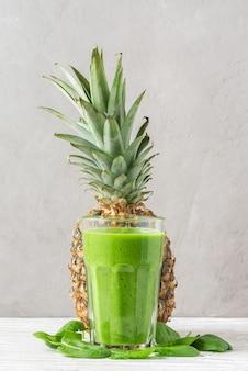 Rauw veganistisch gezond drankje. groene smoothie detox in een glas gemaakt van spinazie, ananas, avocado en chiazaad