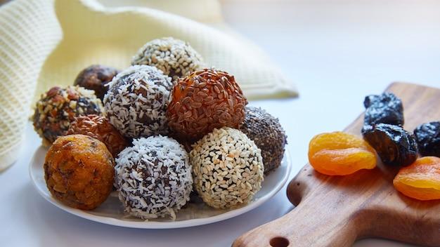 Rauw, veganistisch, gezond voedsel met noten, chiazaad, sesamzaad, vlas, kokosvlokken en gedroogd fruit, gedroogde pruimen en gedroogde abrikozen