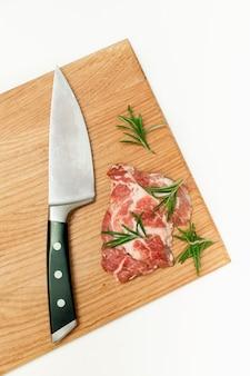 Rauw vers rundvlees biefstuk met rozemarijn en mes op snijplank geïsoleerd op een witte achtergrond, kopieer ruimte, voedsel thuis koken, bovenaanzicht.