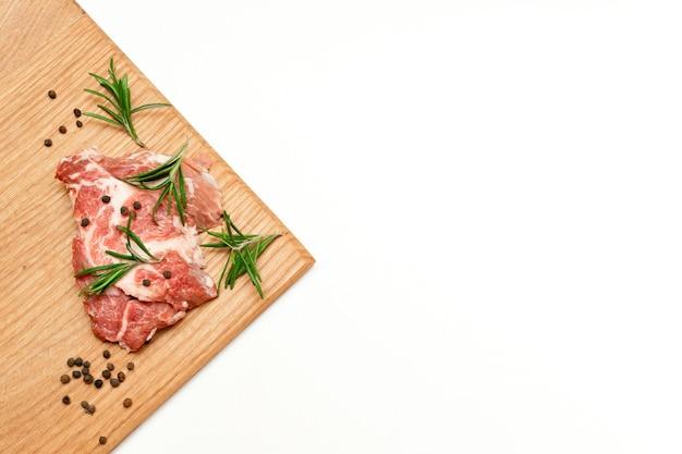 Rauw vers rundvlees biefstuk met rozemarijn en peper op snijplank geïsoleerd op een witte achtergrond, kopieer ruimte, eten thuis koken.