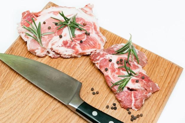 Rauw vers rundvlees vlees steaks met rozemarijn, peper en mes op snijplank geïsoleerd op een witte achtergrond close-up voedsel koken thuis.
