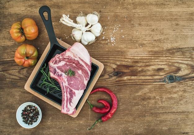 Rauw vers vlees ribeye steak met peper, zout, chili, knoflook, erfgoed tomaten en rozemarijn in pan over rustieke houten, bovenaanzicht.