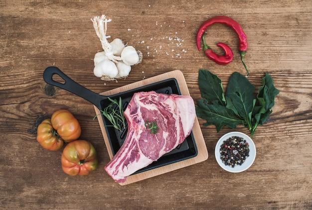 Rauw vers vlees ribeye steak met peper, zout, chili, knoflook, spinazie, heirloom tomaten en rozemarijn in kookpan