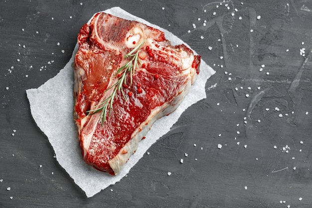 Rauw vers vlees t-bone steak met kruiden op een donkere achtergrond