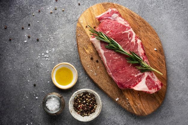Rauw vlees biefstuk op een houten bord met kruiden en olie