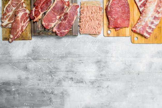 Rauw vlees. de verschillende soorten vlees van varkensvlees en rundvlees. op een rustieke achtergrond.