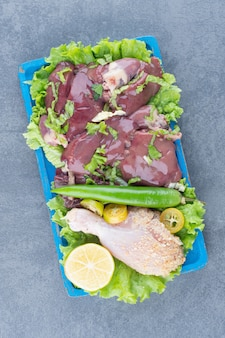 Rauw vlees en kippenbeen op blauw bord.