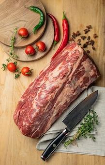 Rauw vlees gesneden stukjes rundvlees met specerijen en kruiden op een houten bord